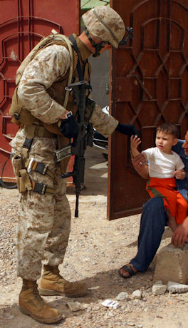 US military propaganda photo of US soldier giving candy (or is it cigarettes) to a spotlessly dressed child.